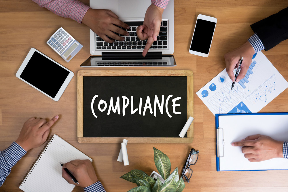 Compliance image with people around a table.
